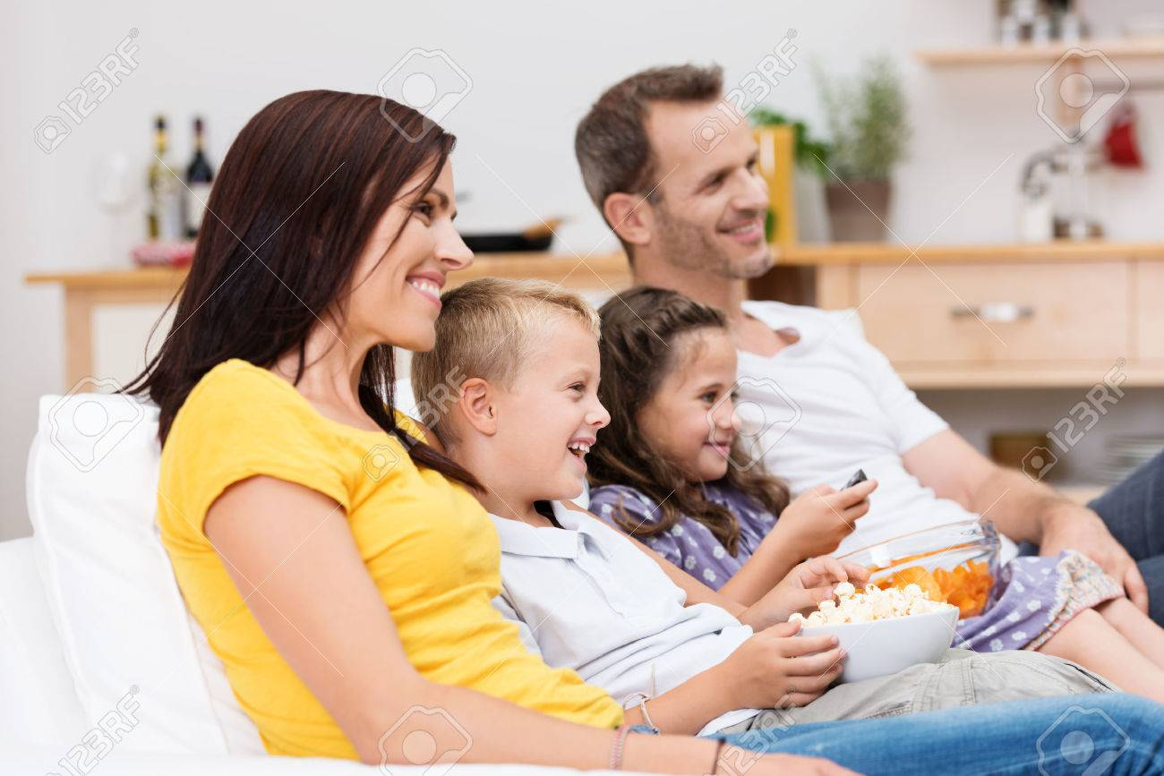 Happy young family watching television with attractive young parents sitting with their two children on a sofa in the living room laughing at the program Stock Photo - 23386709
