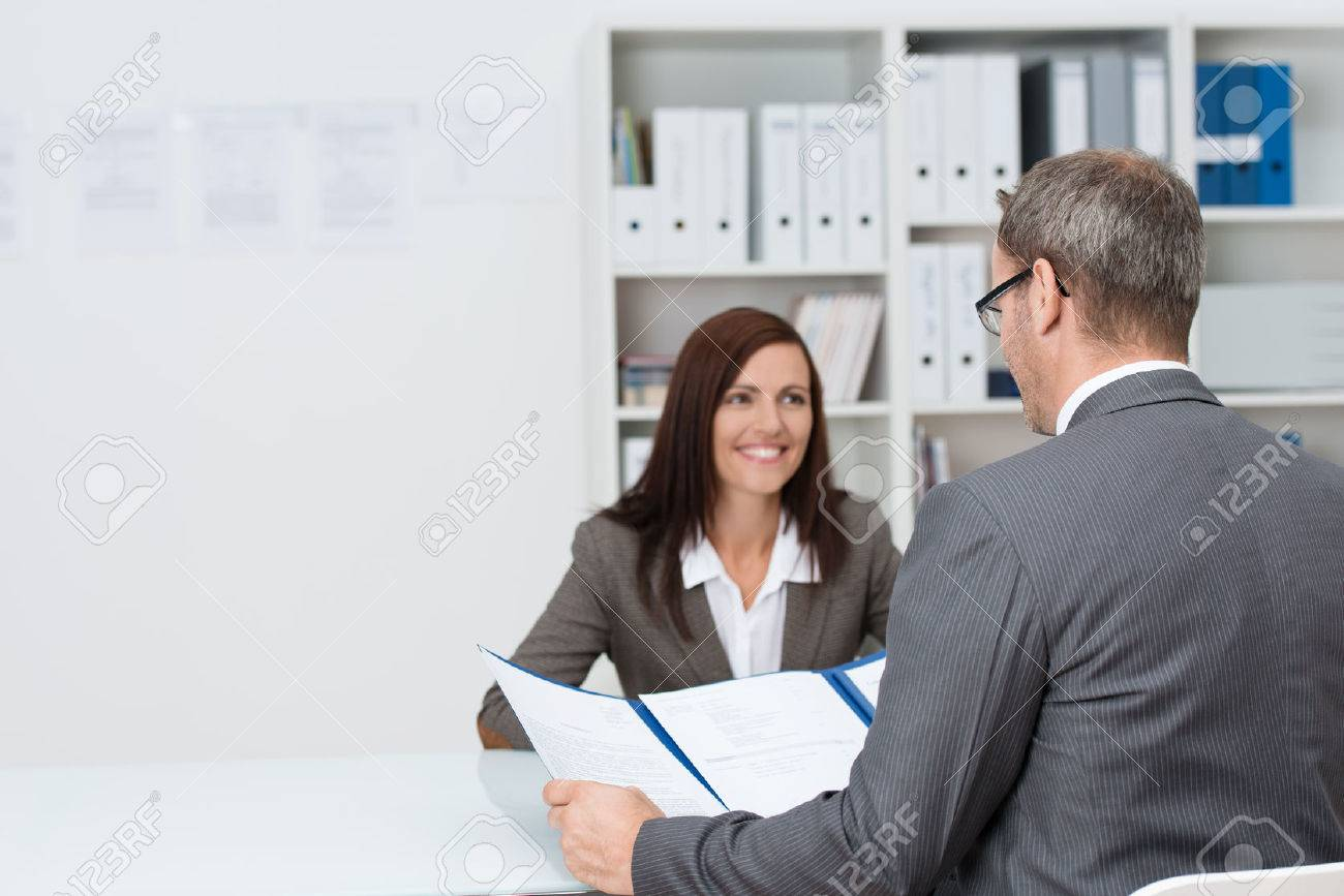 businessman conducting an employment interview an attractive businessman conducting an employment interview an attractive young female applicant sitting opposite him at the