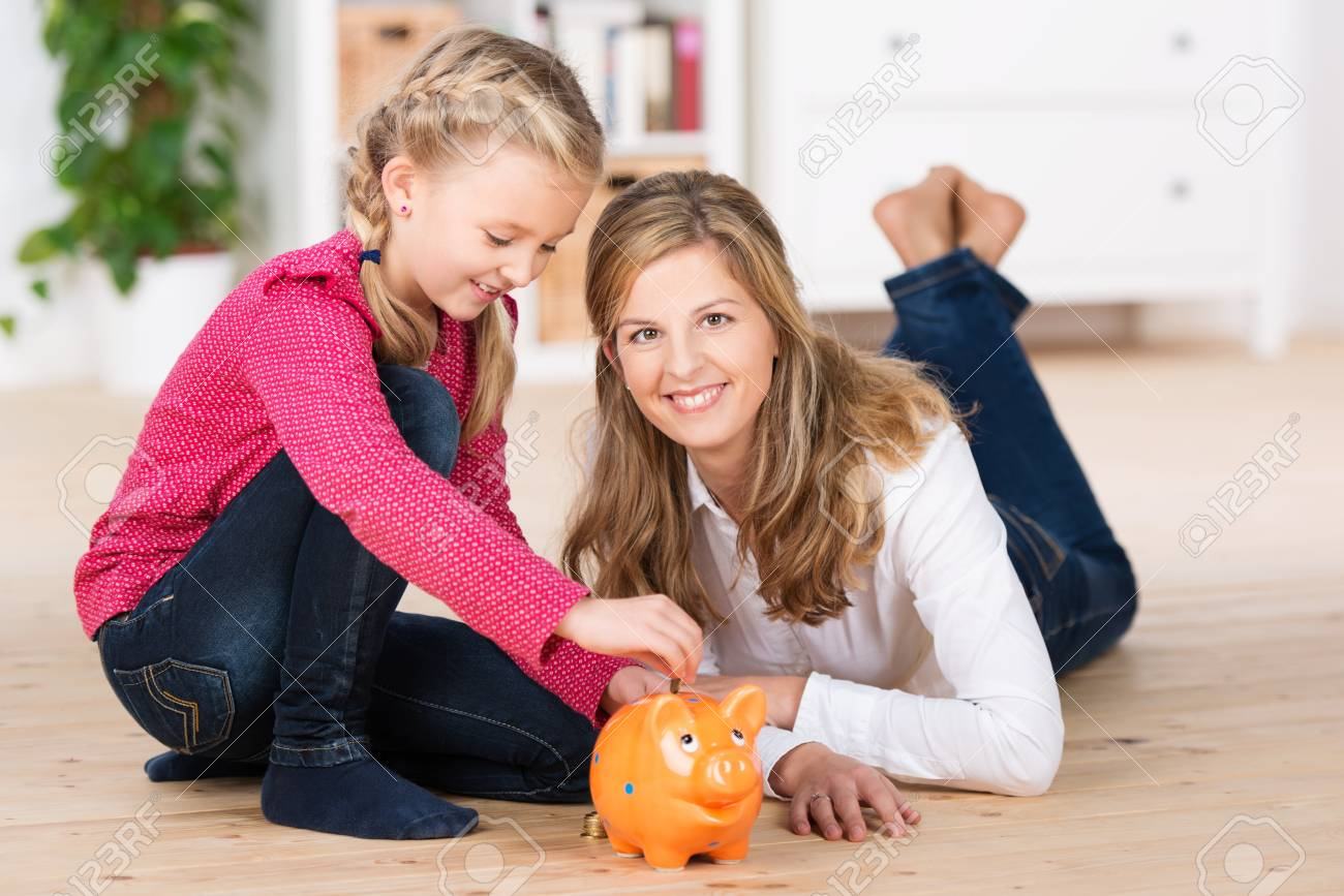 Happy little girl saving her pocket money sitting on the living room floor with her attractive young mother putting coins into the slot of a piggy bank Stock Photo - 23487249