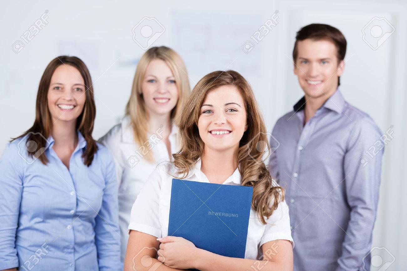 Happy erfolgreiche junge Bewerber, der vor ihrem neuen Arbeitskollegen mit  einem strahlenden Lächeln hielt eine