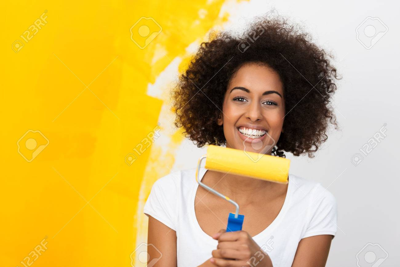 Smiling African American Woman Redecorating Her House Holding A Paint Roller Covered In Orange Paint Which