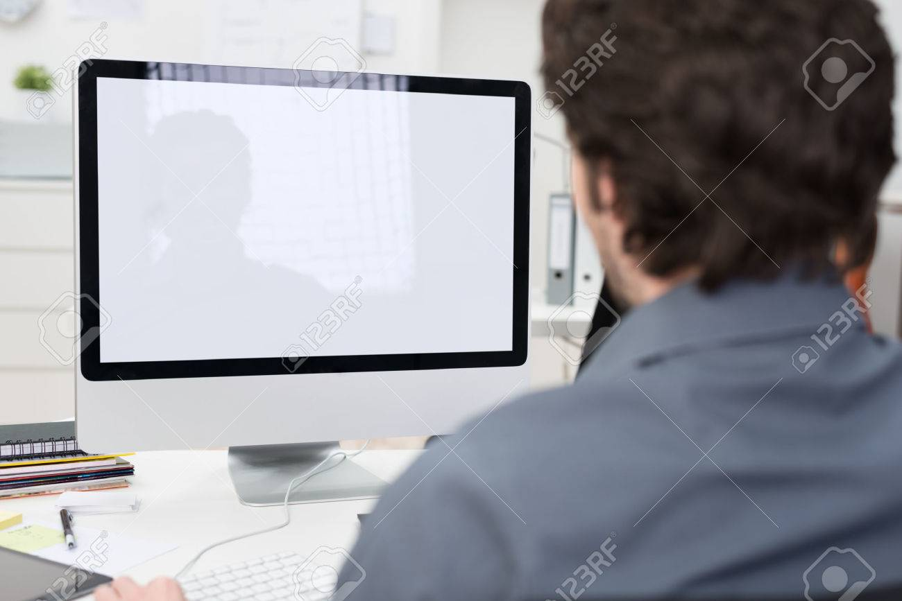businessman using a desktop computer with a view over his shoulder