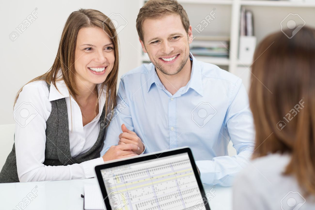 Attractive young couple in a meeting with their business and investment adviser or insurance agent sitting at a desk in her office with happy smiles - 26571613