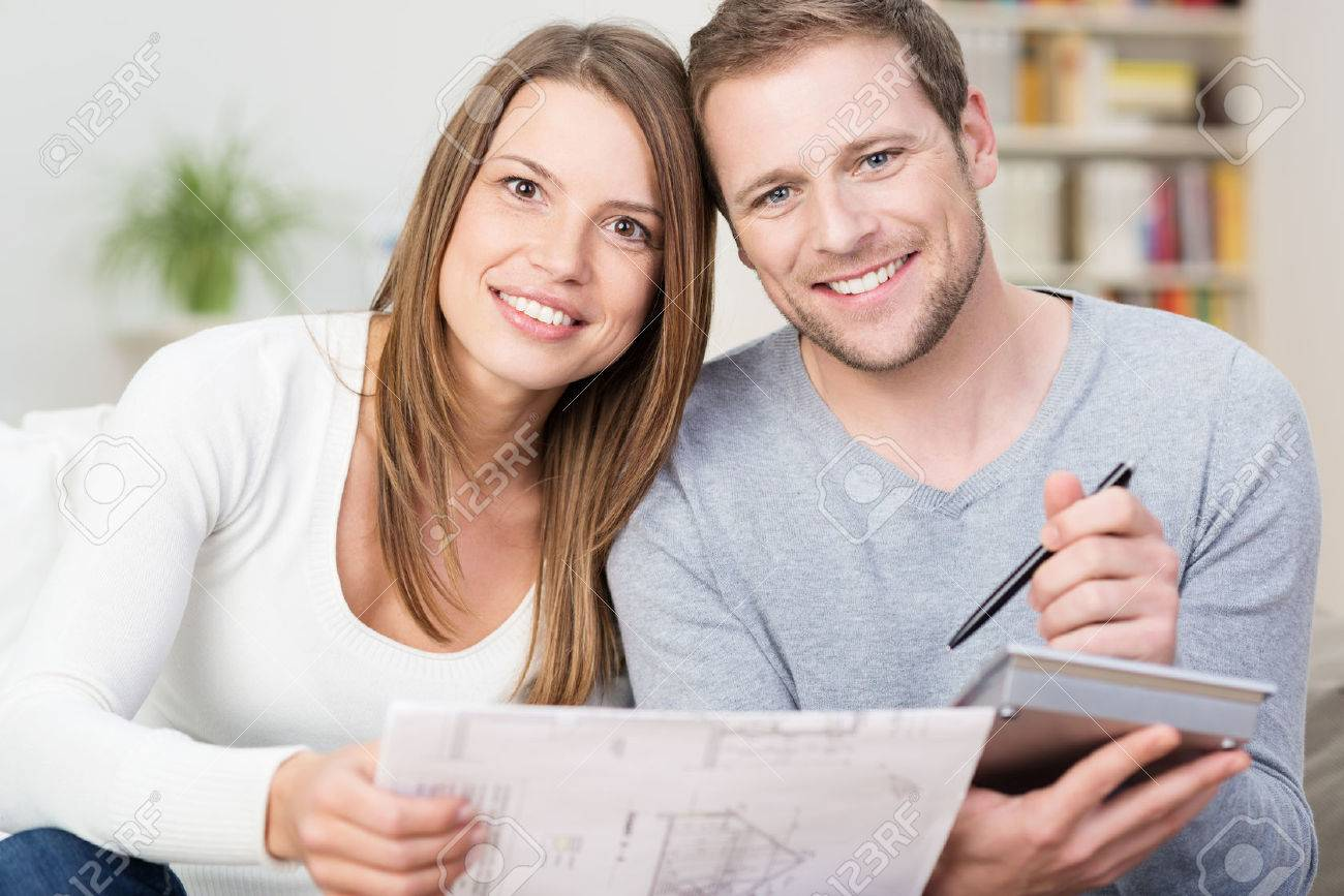 Happy young couple looking at a diagram of a new product together with a calculator to see if they can afford it or if it would be suitable for their house Stock Photo - 27246690