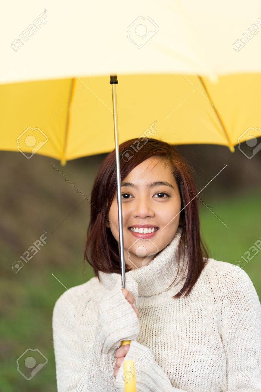 9af068c0af7 Beautiful young Asian woman in a warm winter polo neck sweater under a  yellow umbrella smiling