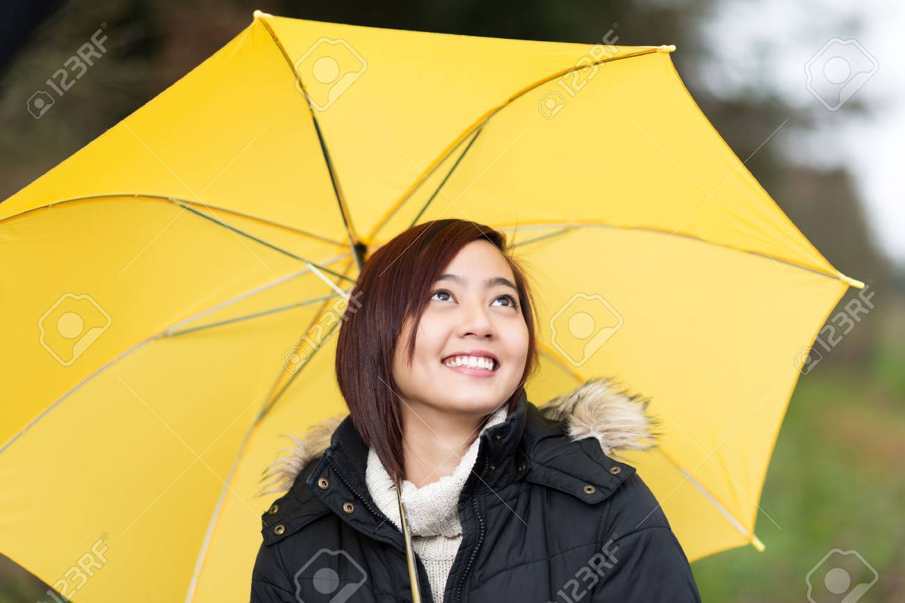 474e0dada68 Happy attractive young Asian woman walking with a yellow umbrella looking  up at the sky with
