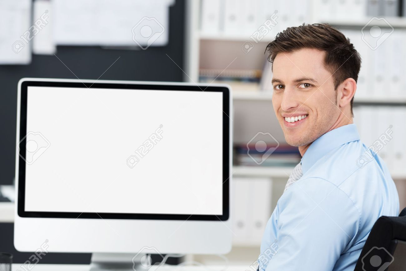 Smiling friendly young businessman sitting in front of a large blank desktop computer monitor turning to look at the camera, screen fully visible - 27688283