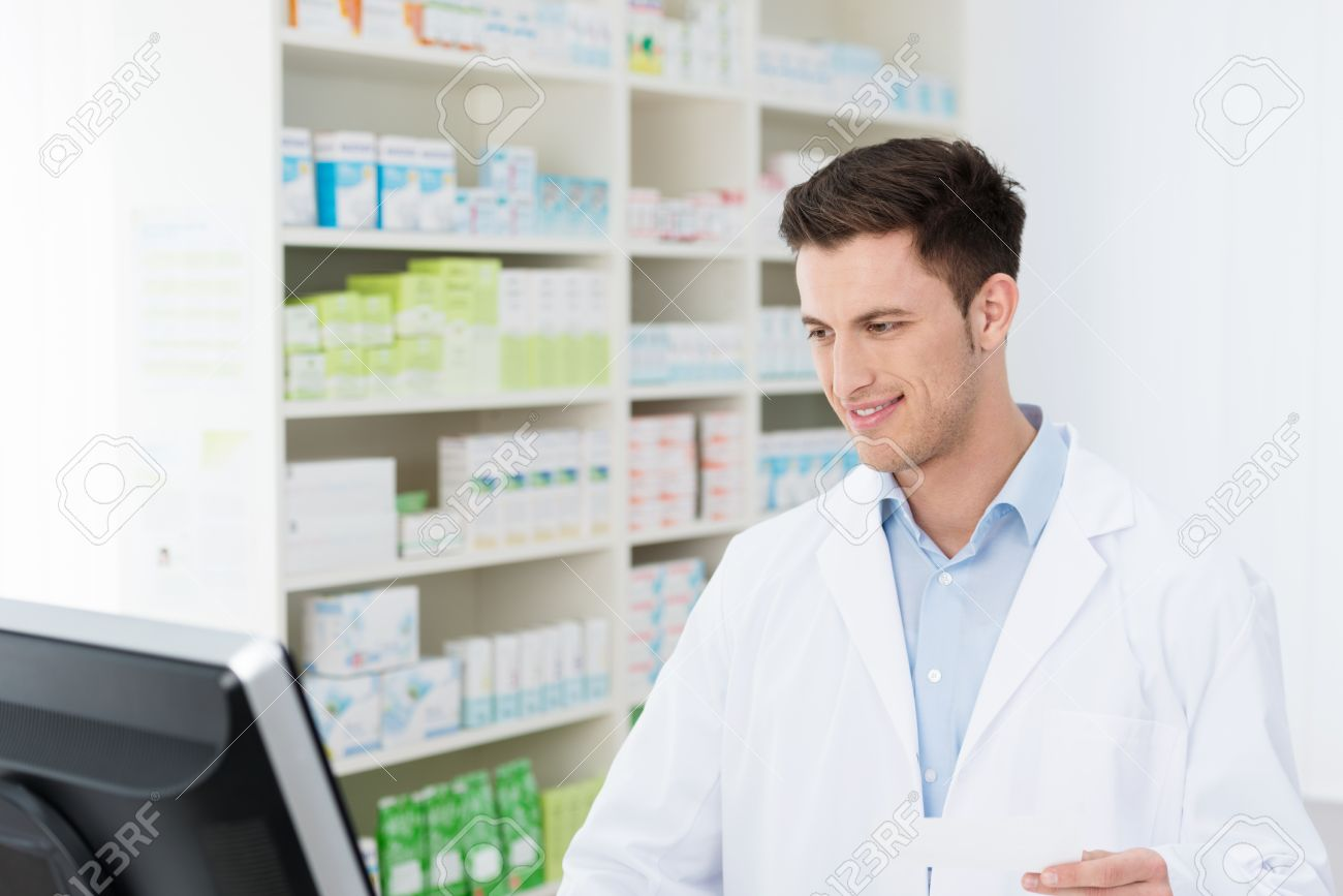 smiling young male pharmacist standing checking stock on his smiling young male pharmacist standing checking stock on his computer in the pharmacy as he prepares