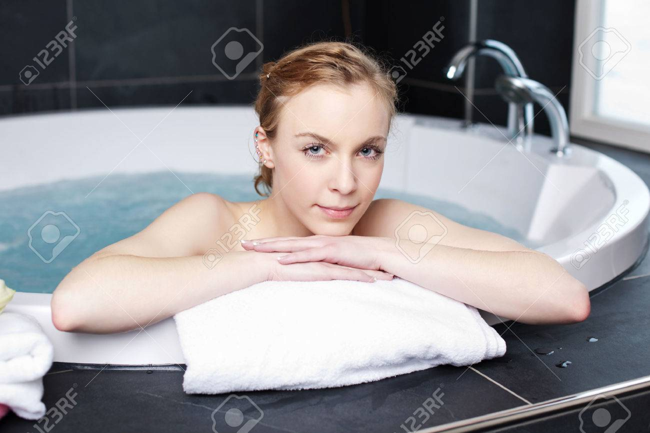 Pretty Woman Soaking In A Spa Bath Resting Her Arms On The Rim Looking At