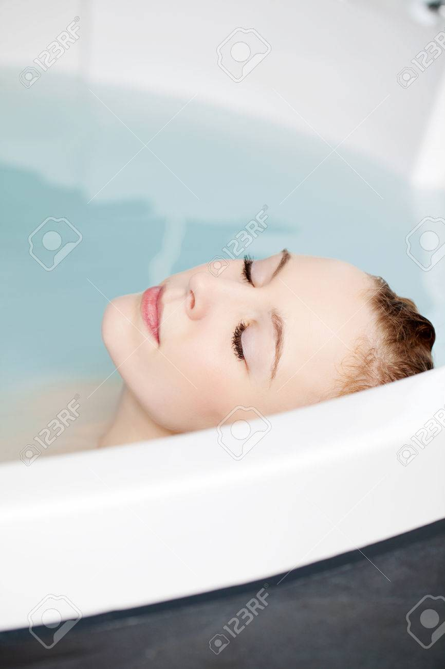 Serene Woman Relaxing In A Round Spa Bath With Her Head Resting ...