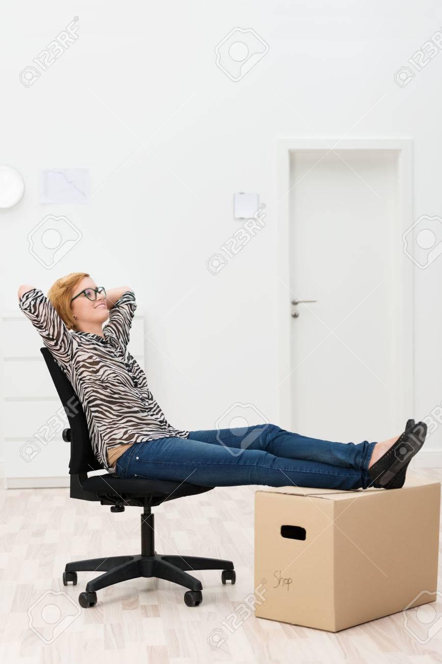 Détente D'emballage Une Nouvelle Femme Assis Sur Carton Maison Avec Ses Pieds De Un Au Bureau Dans Chaise Sa Ou ARj3L54