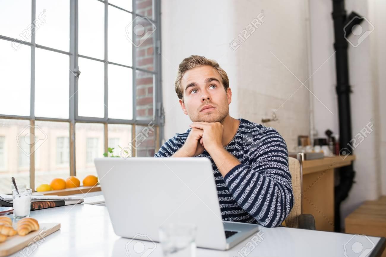 Junger Mann Sitzt In Der Küche Seiner Wohnung Denken An Seinem ...