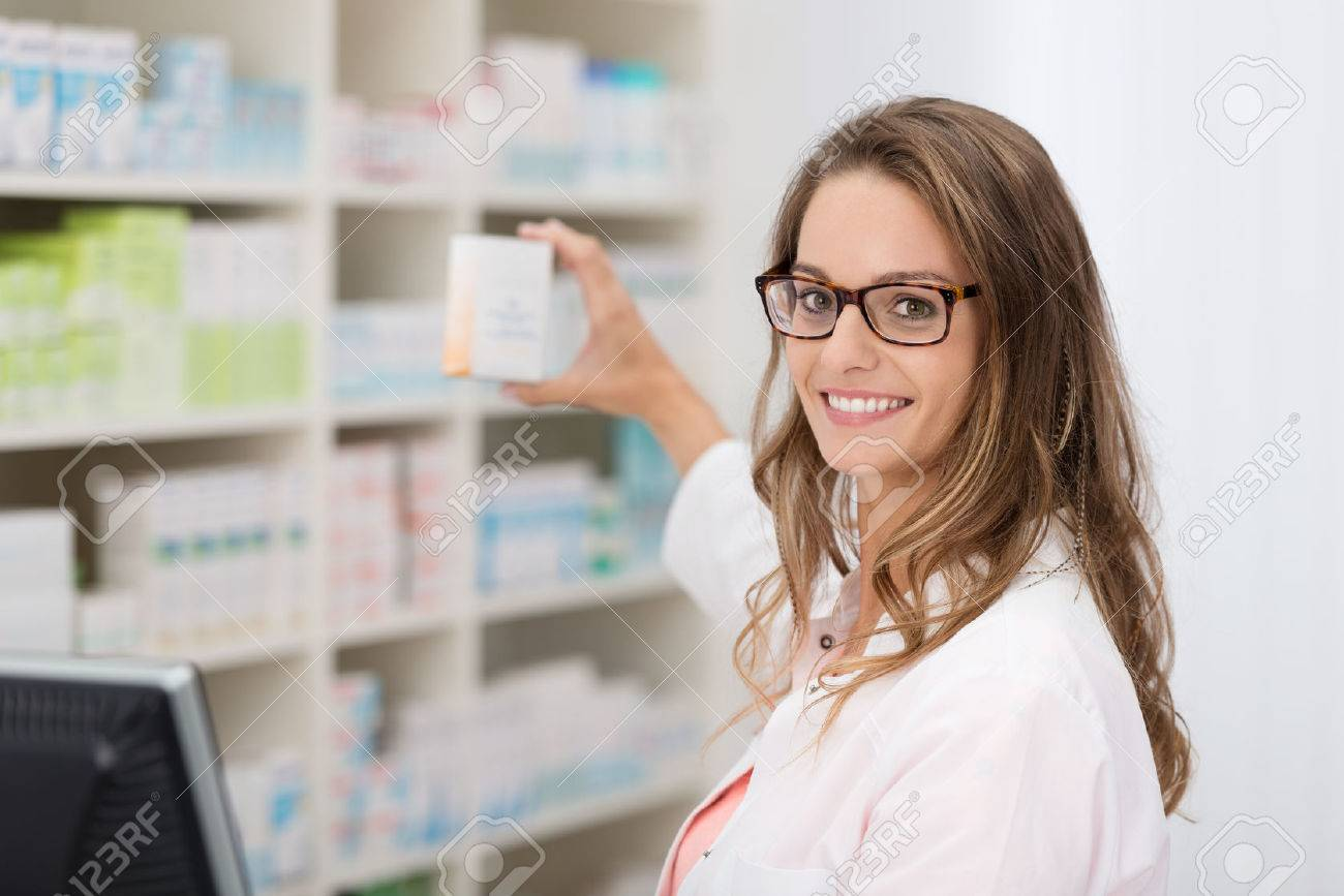 Smiling attractive young female pharmacist promoting a product in a blank white box she is holding up in her hand in the pharmacy - 34559856