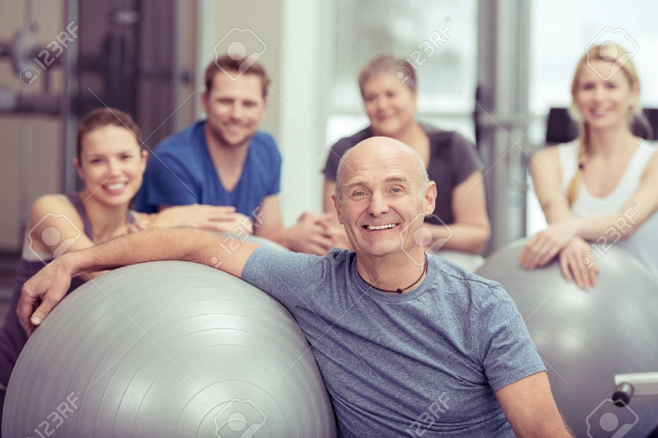 Smiling happy fit senior man in a gym class with a group of diverse people leaning on a pilates ball looking at the camera in a healthy lifestyle concept - 35556085