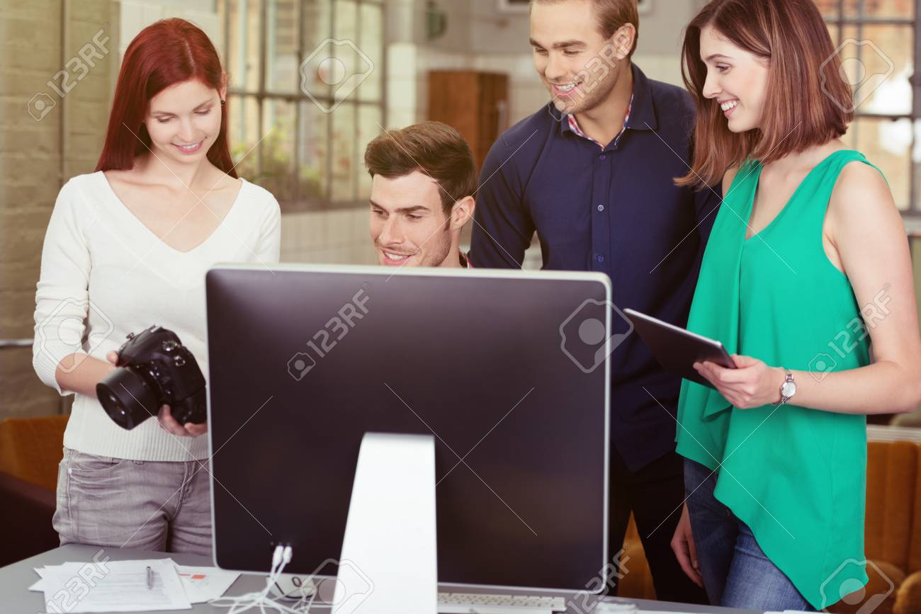 group of young friends watching photos on a dslr camera together