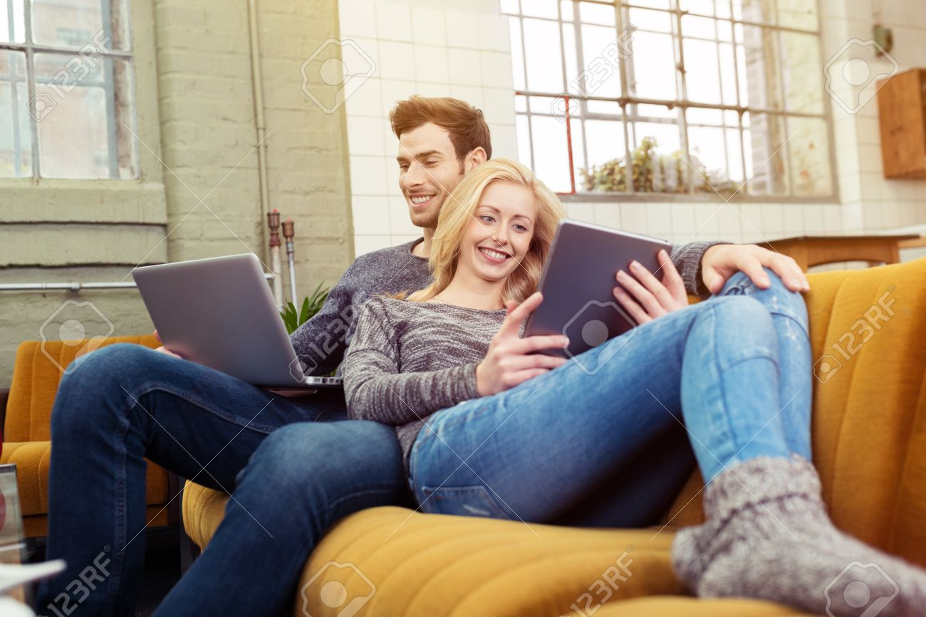 Young Couple Relaxing At Home Catching Up On Social Media As