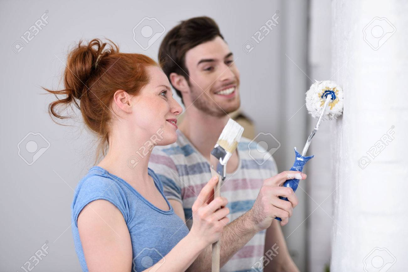Stock Photo Young Couple Redecorating At Home Working As A Team As They Stand Painting A White Wall Together