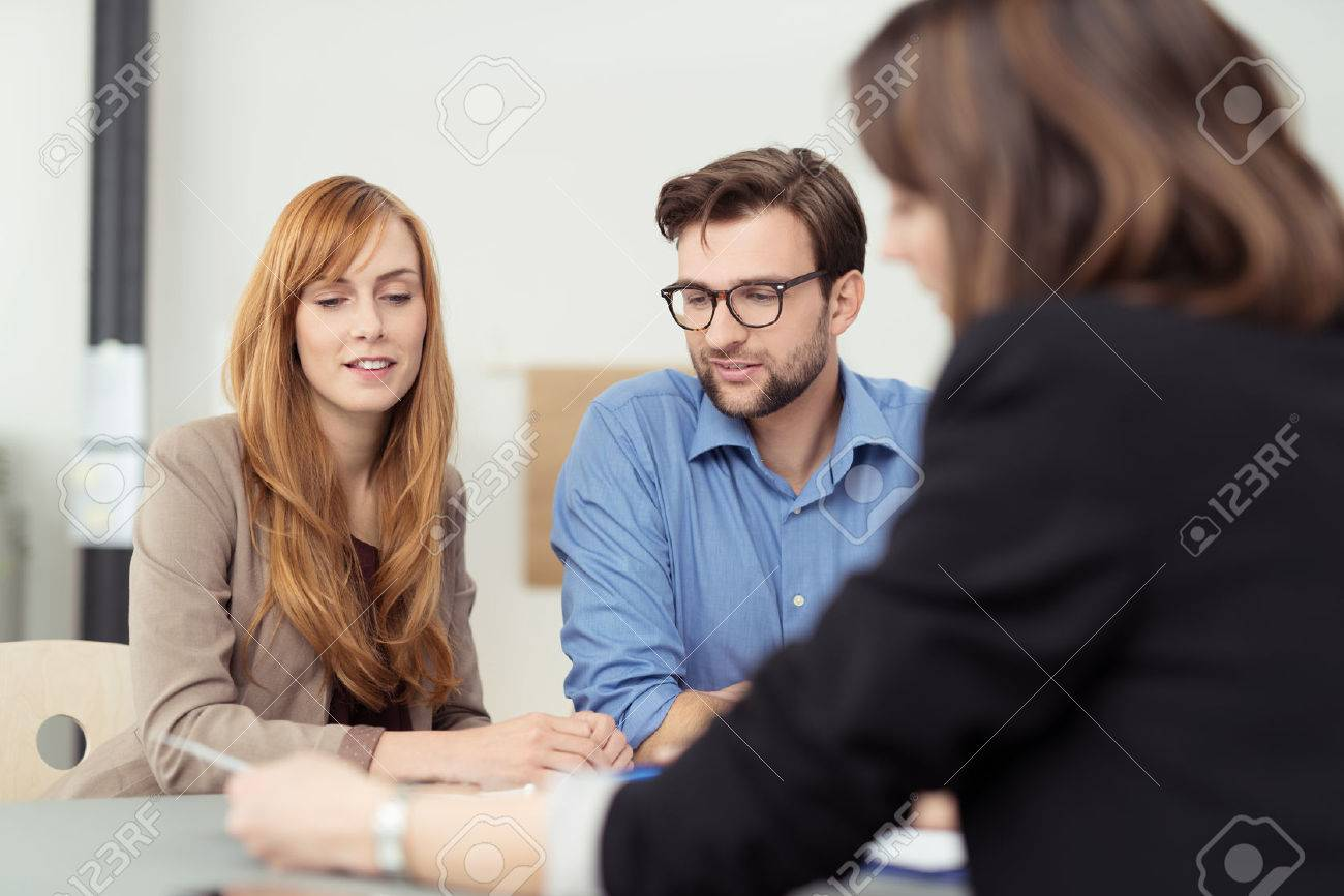 Broker making a presentation to a young couple showing them a document which they are viewing with serious expressions - 40290936