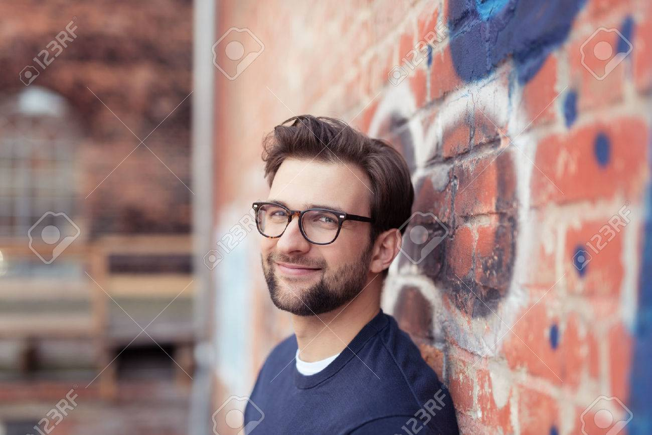 0ee2c4c6b0a Portrait of Smiling Young Man with Facial Hair Wearing Eyeglasses and  Leaning Against Brick Wall Painted