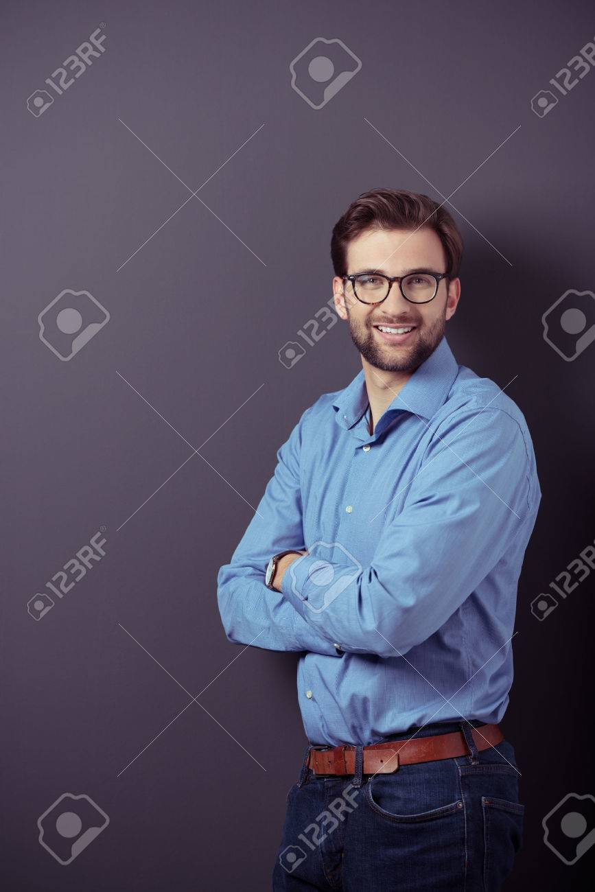 Optimistic Portrait of a Handsome Young Businessman Standing Against Gray Wall with Copy Space While Looking at the Camera with Arms Crossing Over her Stomach. Stock Photo - 40632464