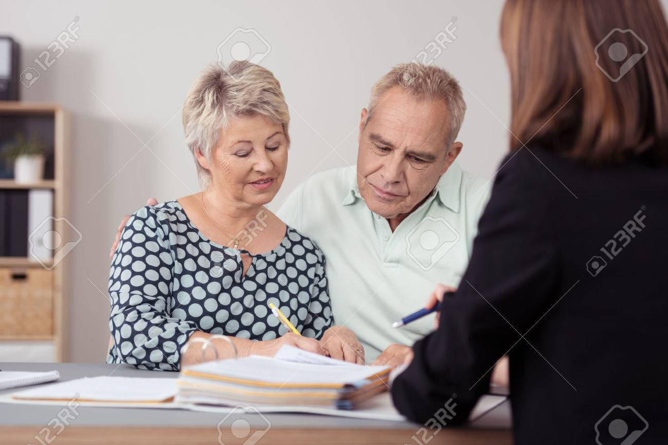 Middle Aged Couple Discussing Something on the Document to a Female Agent at the Table. - 41689841