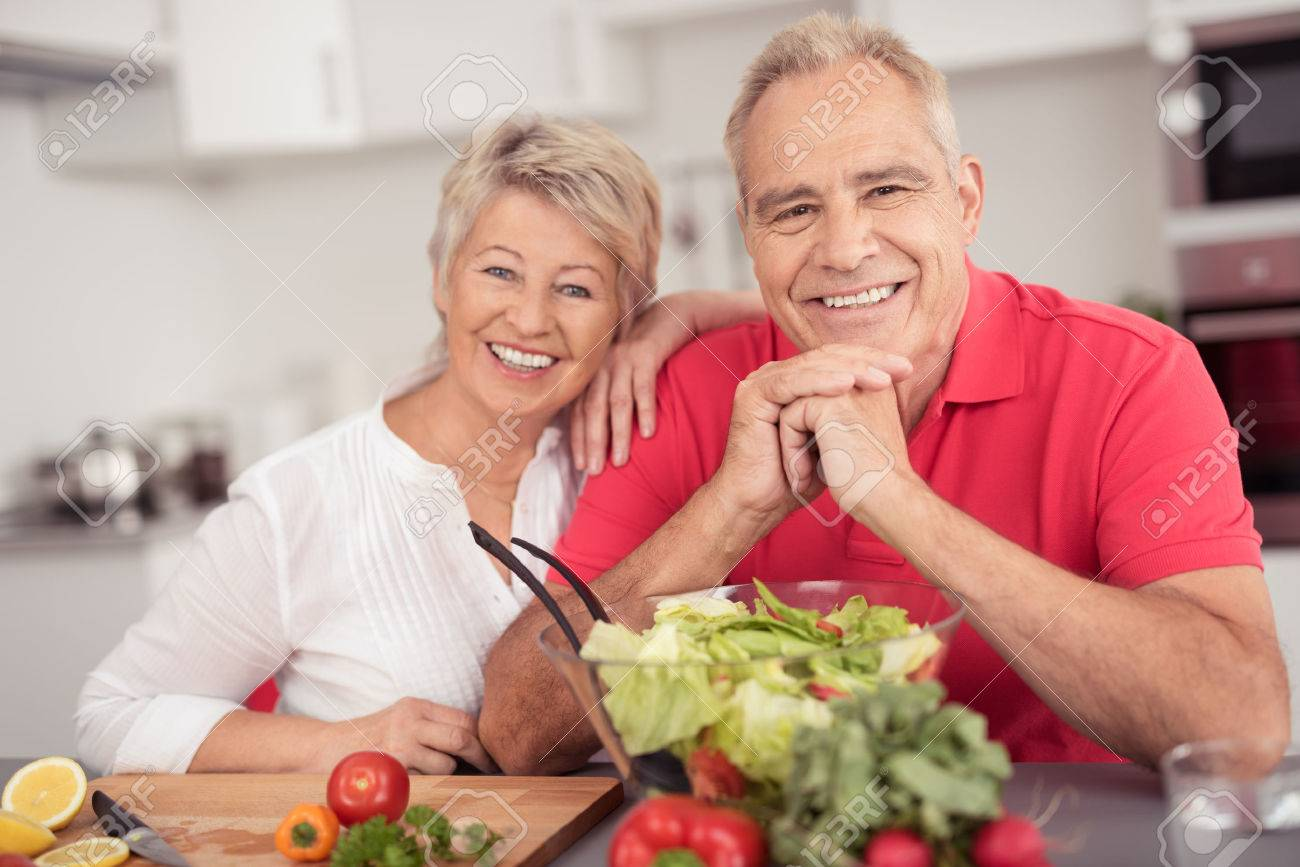 Portrait of a Happy Senior Couple Sitting at the Kitchen Table with a Bowl of Fresh Salad, Smiling at the Camera. - 41689893