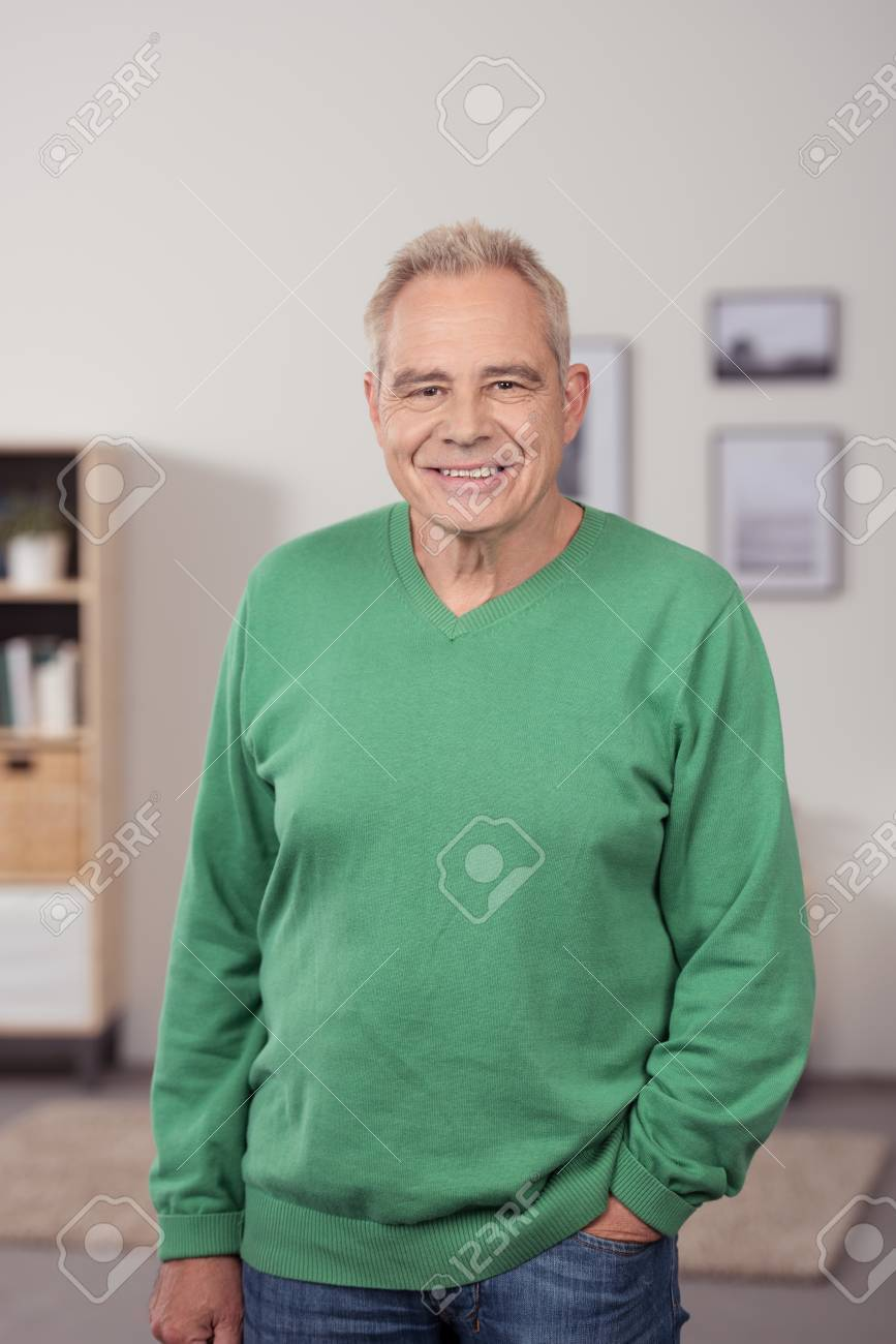 Smiling relaxed senior man standing in his living room with his hand in his pocket looking at the camera - 41689971