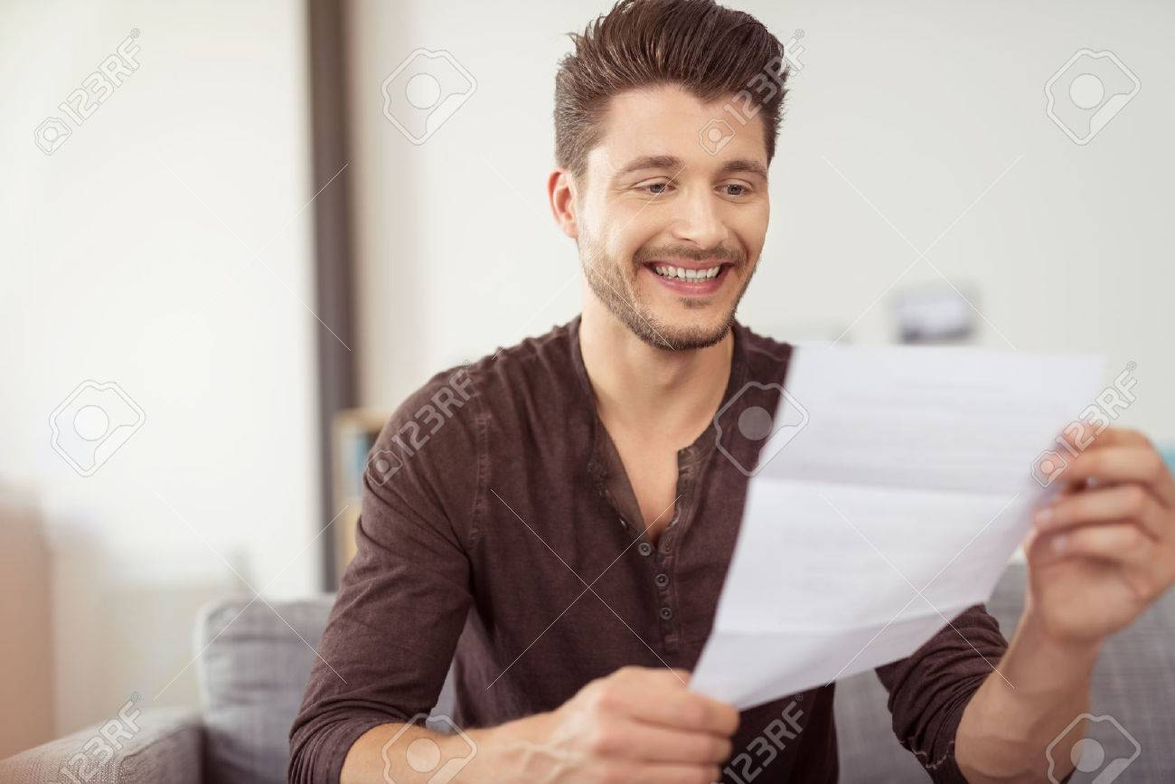 Close Up Good Looking Young Bearded Guy Reading A Letter At The