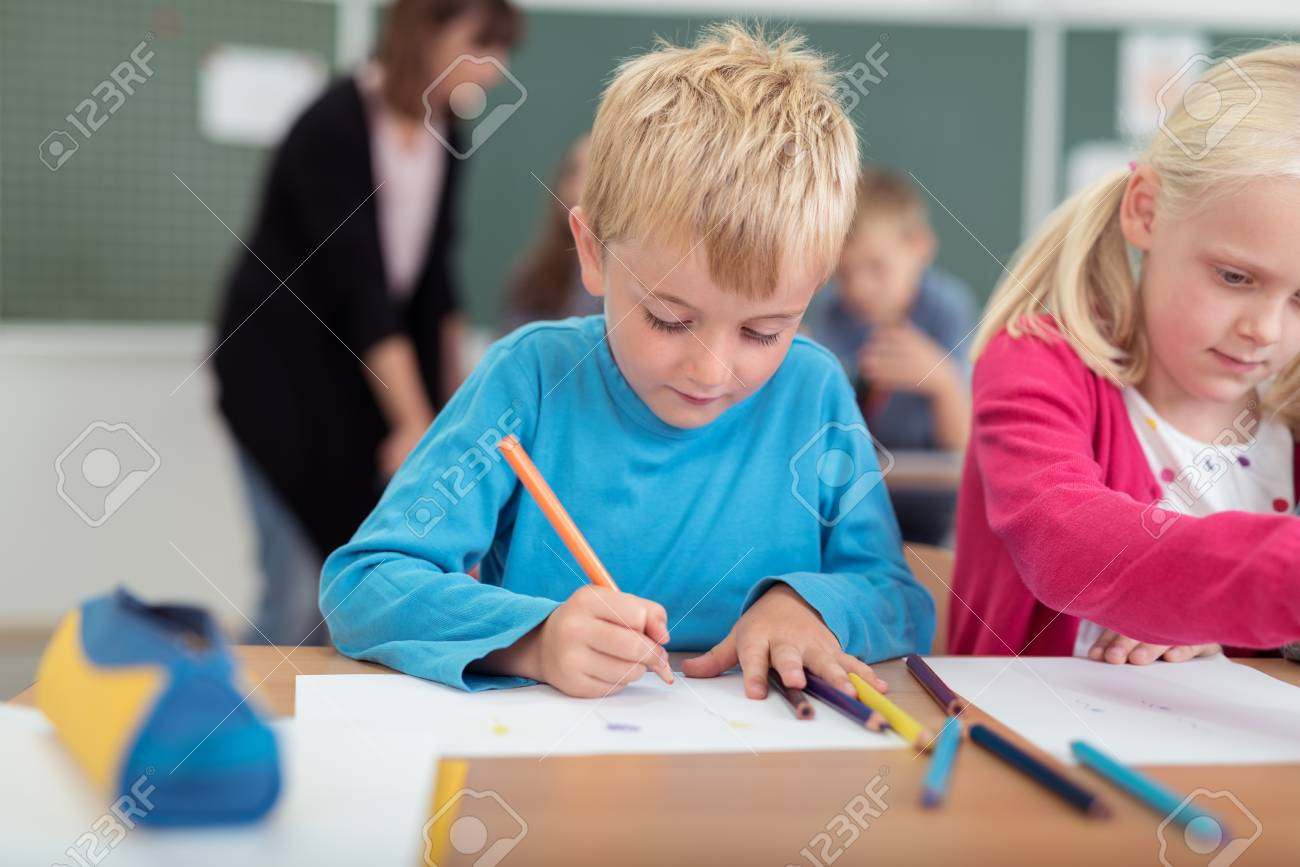 Little Boy And Girl In Kindergarten Class Sitting At A Desk Writing ...
