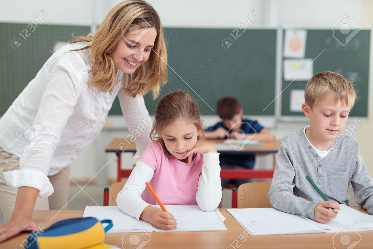 lassroom girls Smiling attractive female teacher checking on a little girls work as she  sits alongside a small