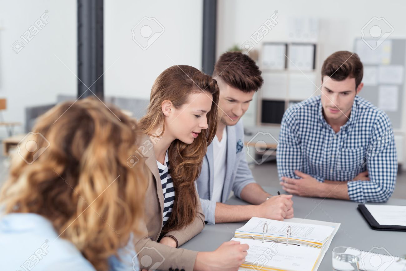 the office the meeting. Young Office Workers In A Meeting Inside The Office, Reviewing Compiled Documents On Top