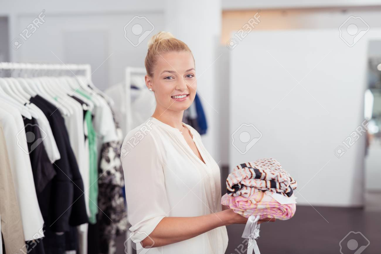 d6f3de201f6 Half Body Shot of a Pretty Young Woman Holding a Pile of Clothes Inside the  Clothing
