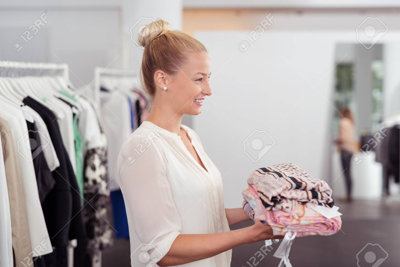 49bf0eb8f11 Half Body Side View Shot of a Pretty Young Woman Holding a Pile of Clothes  to