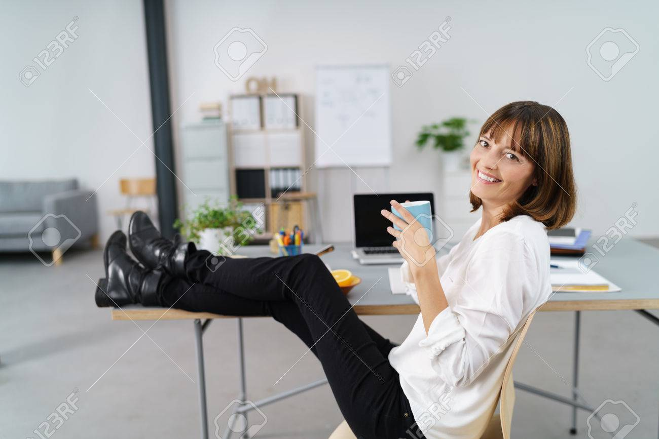 hot office pic. Woman Relaxing At The Office With Her Feet Up On Table And A Cup Of Hot Pic