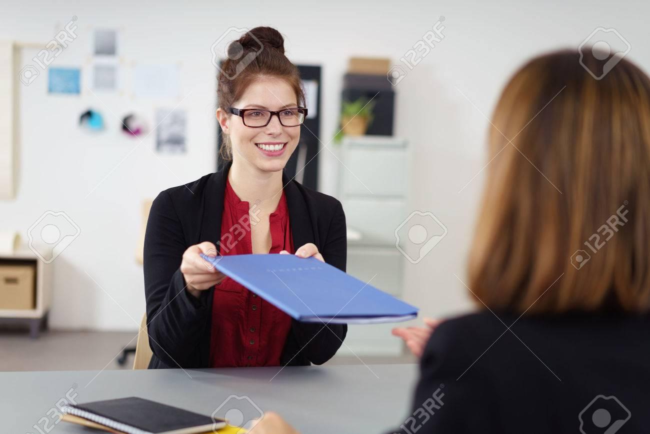 Recht junger weiblicher Bewerber Übergabe ihren Lebenslauf an die  Personalreferent bei der Firma mit einem freundlichen
