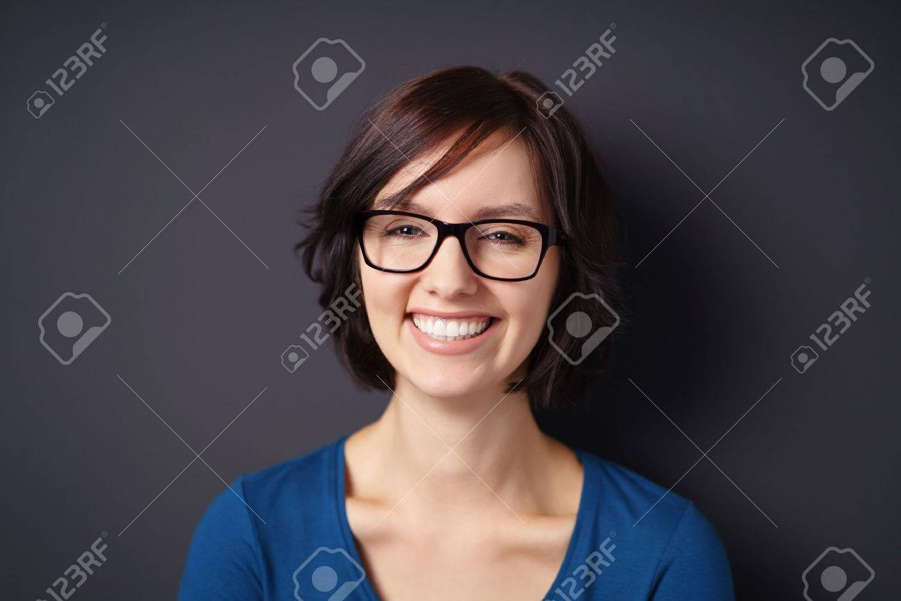 Close up Happy Young Woman, Wearing Eyeglasses, Showing Toothy Smile at the Camera Against Gray Wall Background. Standard-Bild - 48654607