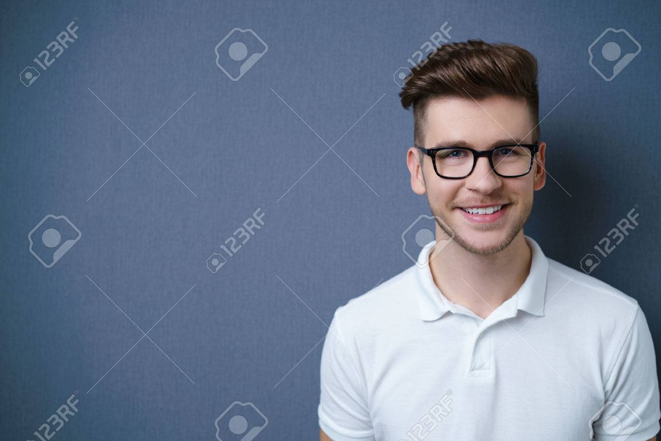 Smiling friendly attractive young man with a modern trendy hairstyle posing against a dark grey background with copyspace, head and shoulders portrait Stock Photo - 49085474
