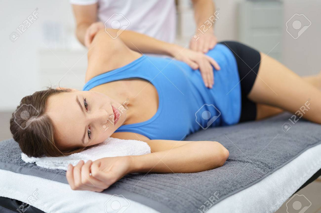 Young Woman Lying on her Side on bed While the Physical Therapist is giving a Treatment to her Injured Body. Stock Photo - 49086007