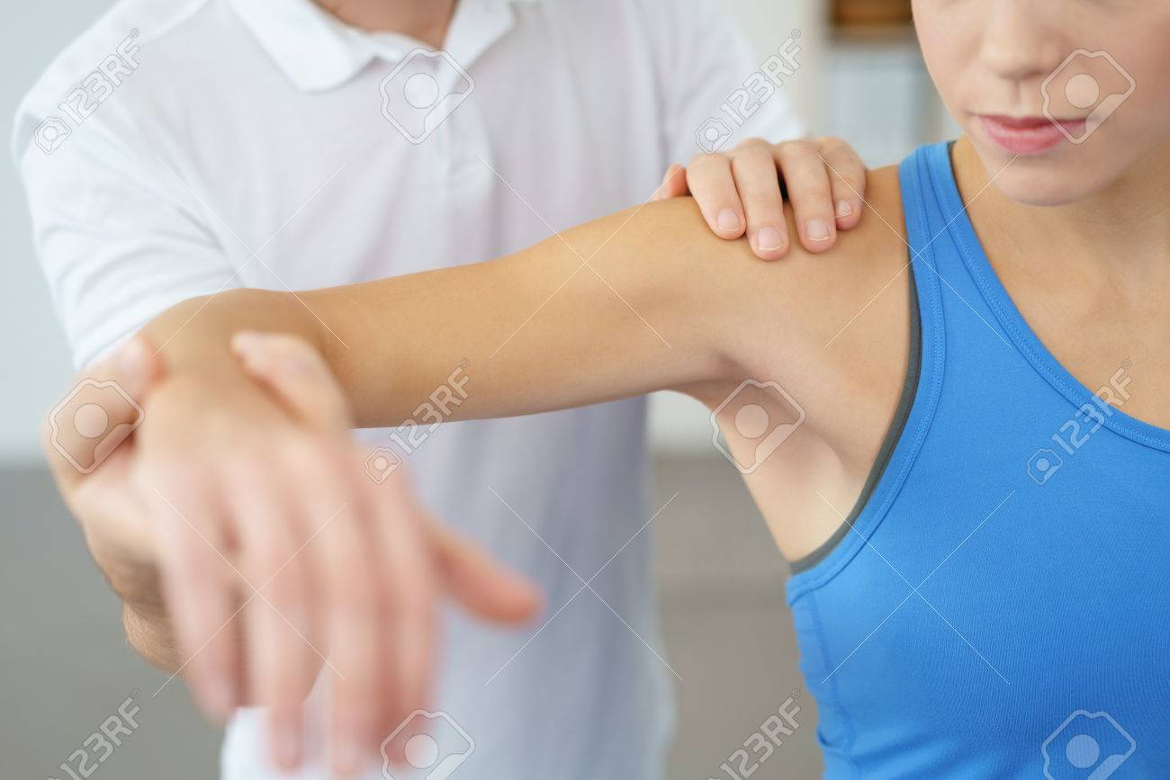 Close up Professional Physical Therapist Lifting the Arm his Female Patient While Examining the Injured Shoulder. Stock Photo - 49086033