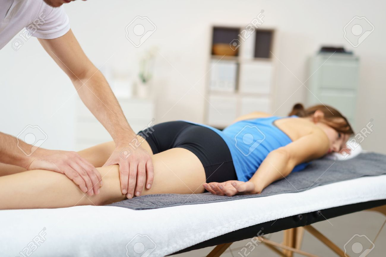 Massage Therapist Massaging the Legs of a Woman Lying Prone on the Bed. Stock Photo - 49086163