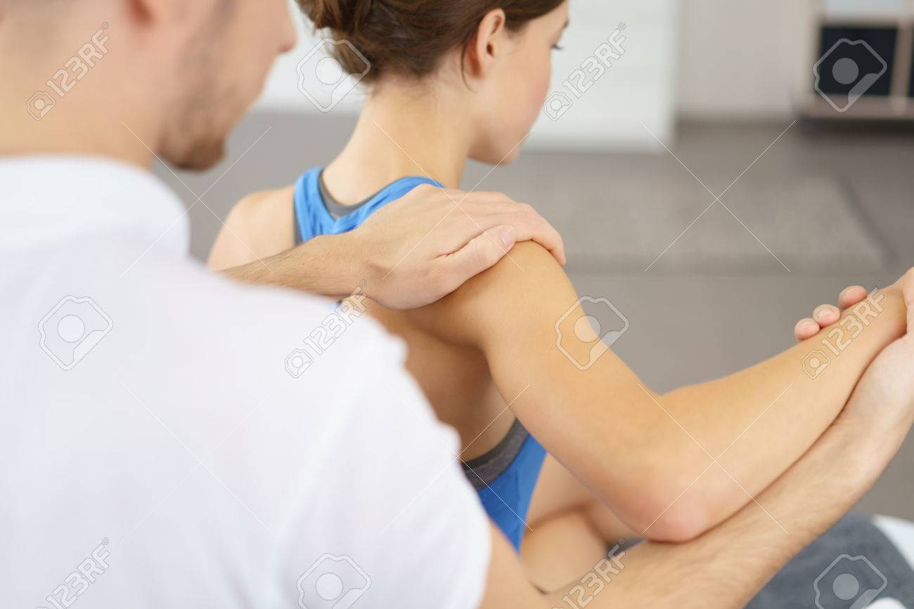 Male Physical Therapist Massaging the Injured Arm and Shoulder of a Young Woman Slowly. Standard-Bild - 49086197