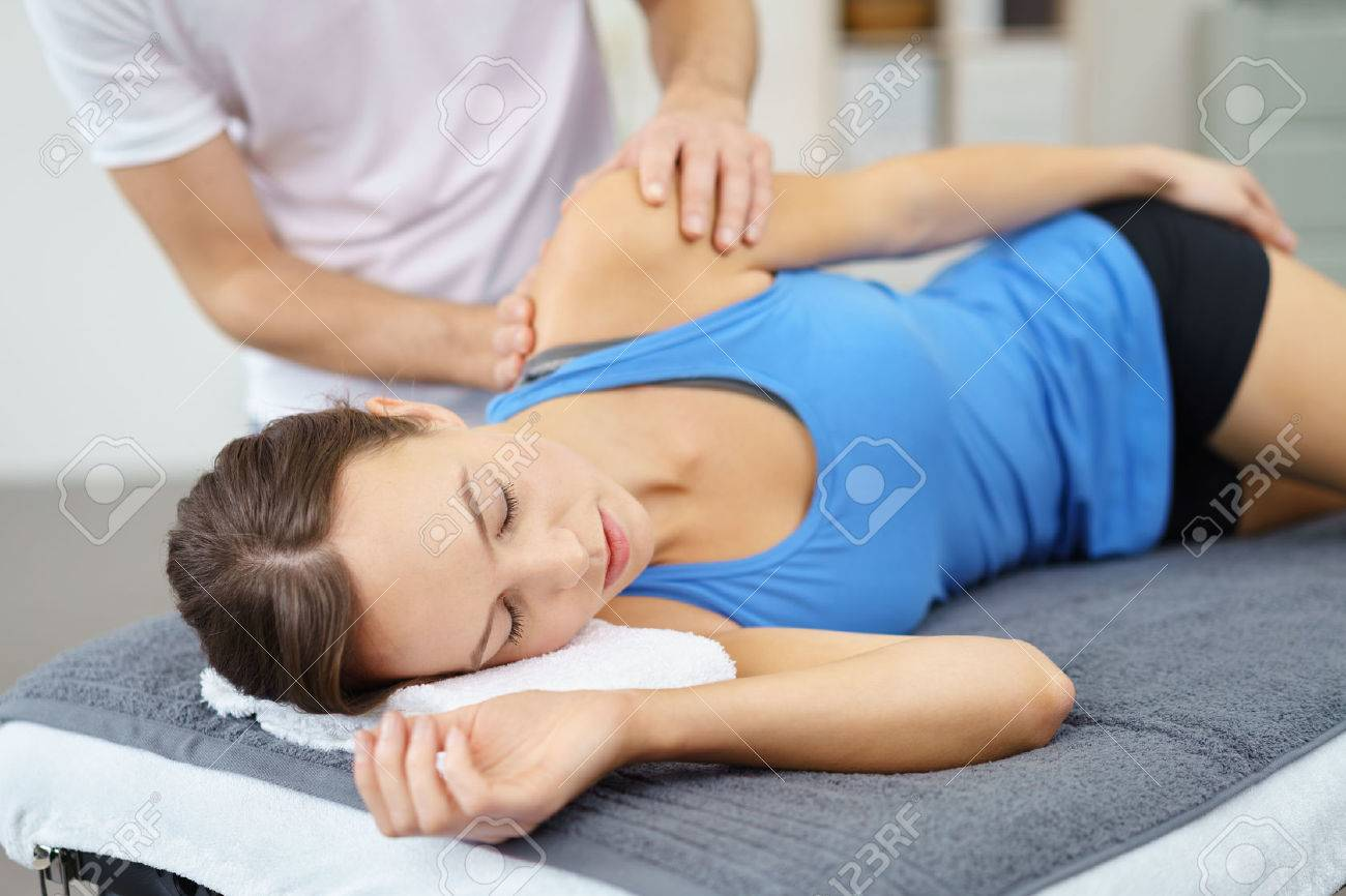 Young Woman Lying on Bed While her Physical Therapist is Giving a Massage to her Injured Shoulder. Stock Photo - 49086205