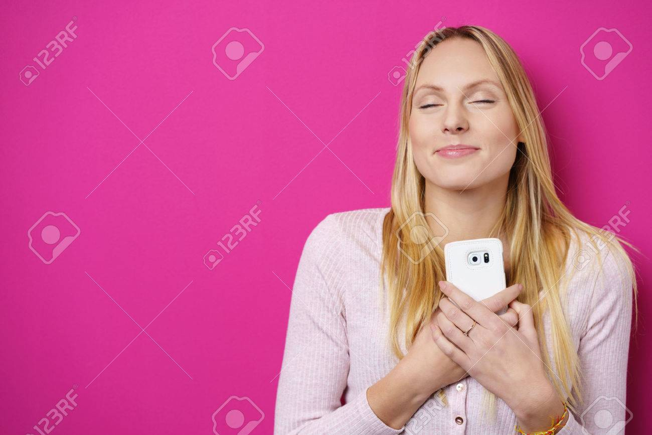 Dreamy romantic young woman holding a mobile phone clasped to her chest and heart with a lovely smile of pleasure and her eyes closed in bliss, over a bright pink or magenta background with copy-space Stock Photo - 50106431