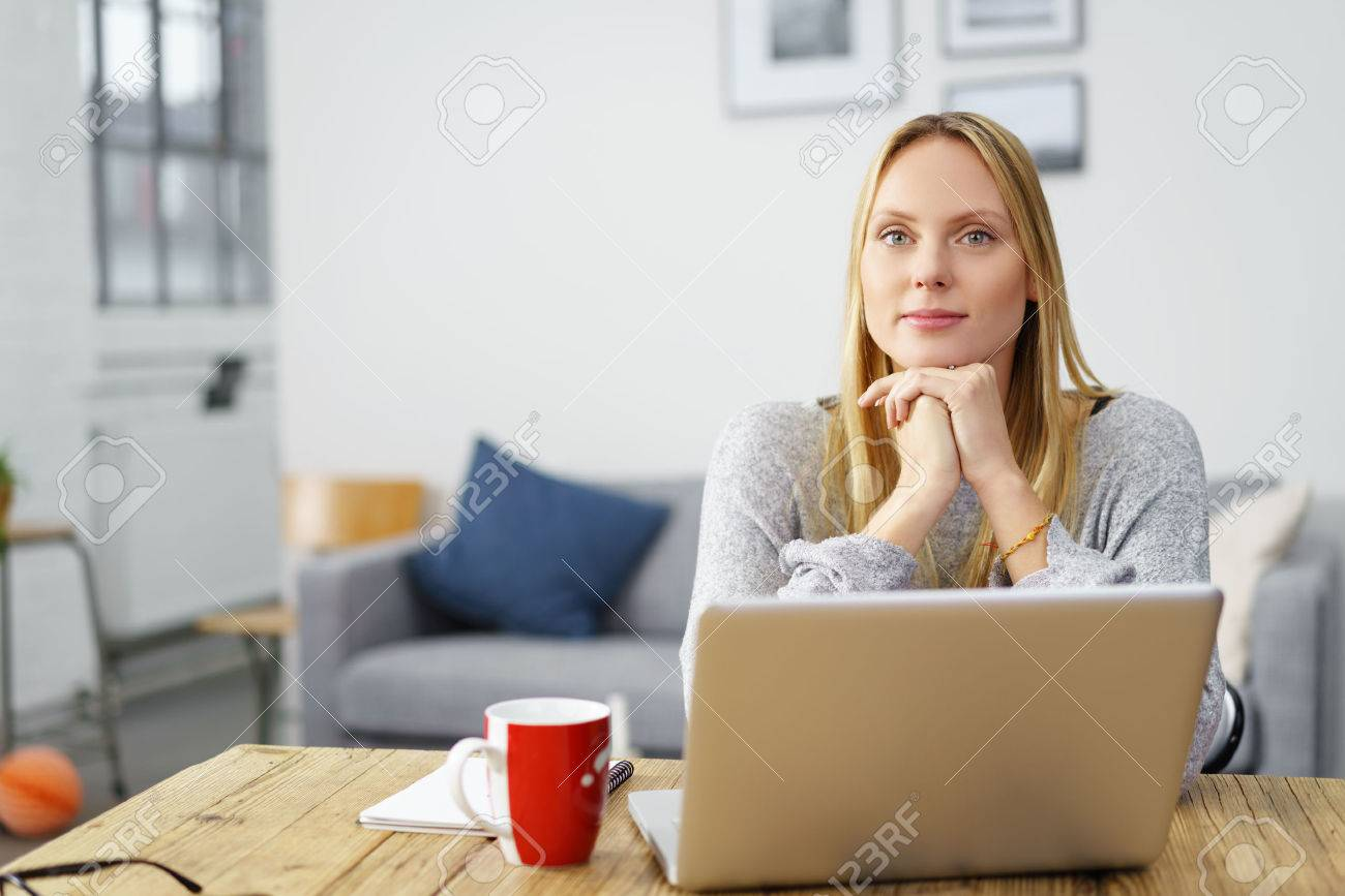 confident young woman sitting at home with her notebook with her chin on her hands - 50106675
