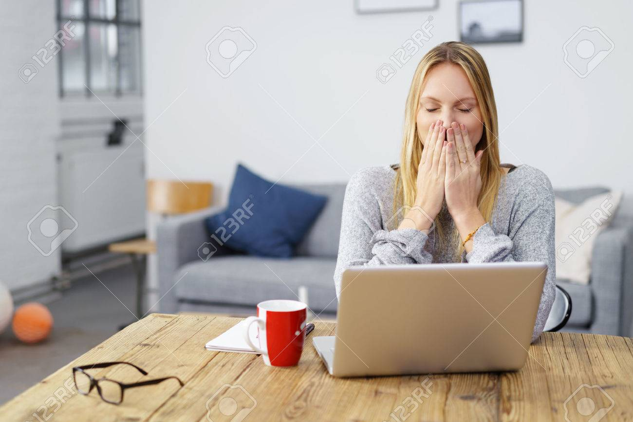 woman sitting at laptop at home holding her hands on her mouth afraid of a computer virus or a mistake Standard-Bild - 50106699