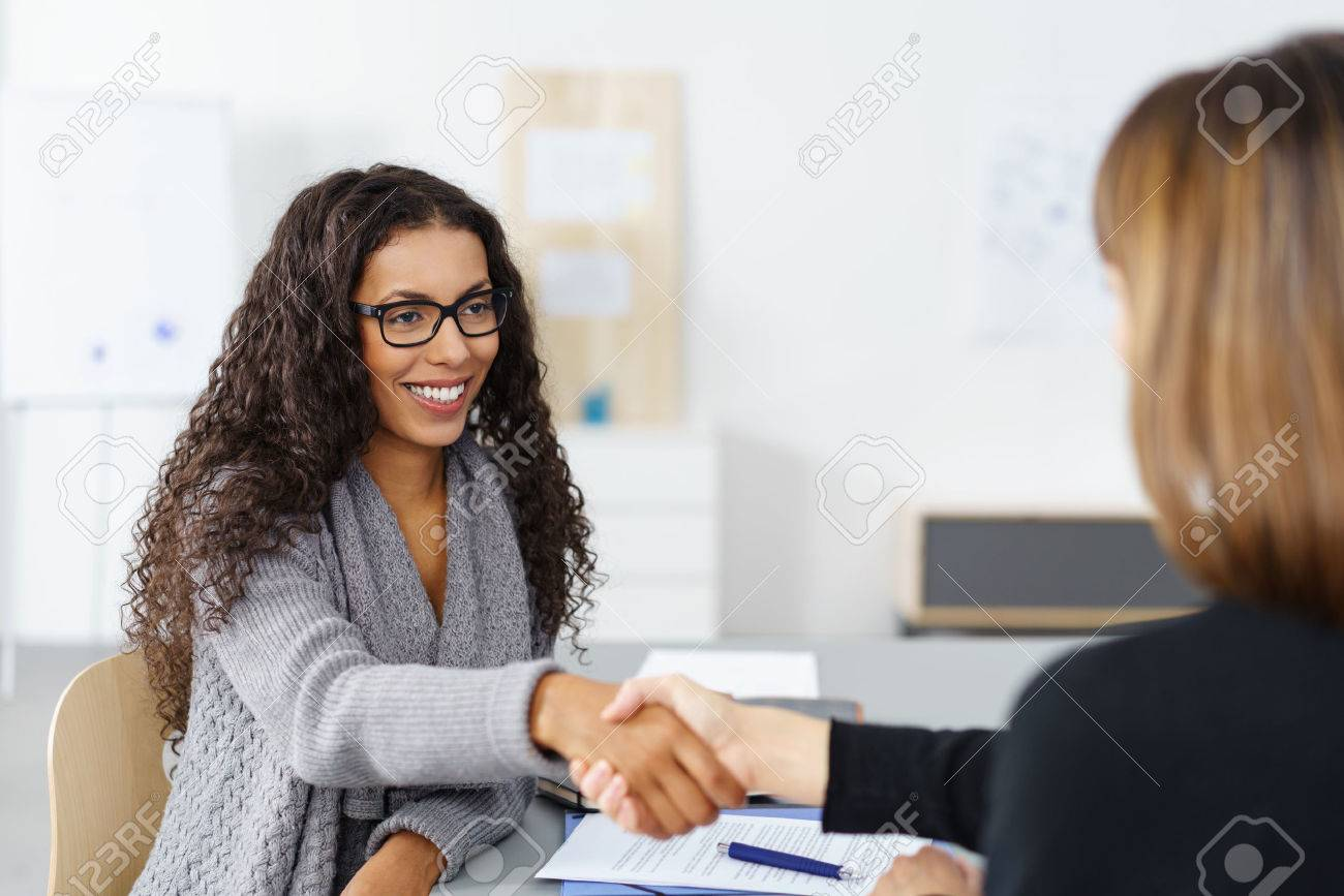 Two businesswomen shaking hands over a desk as they close a deal or partnership, focus to a smiling young African American lady Stock Photo - 50615952