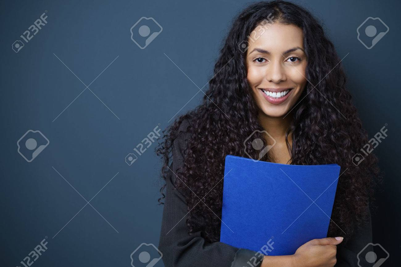 Motivated young African American job seeker clutching a blue CV in her hands standing against a blue background with copy space beaming at the camera Stock Photo - 50615986