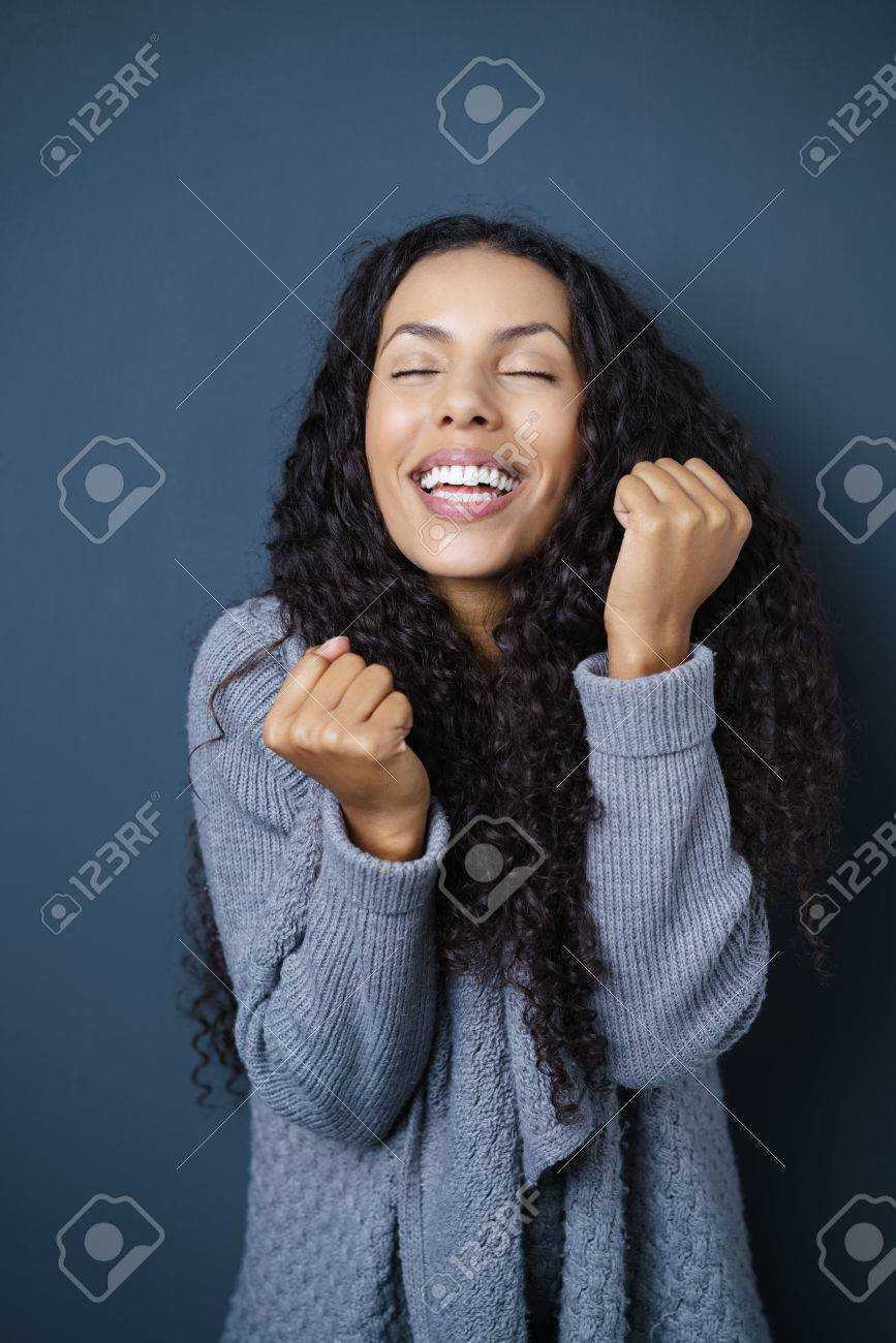 Excited attractive young African American woman cheering and clenching her fists in jubilation, dark studio background - 50616454