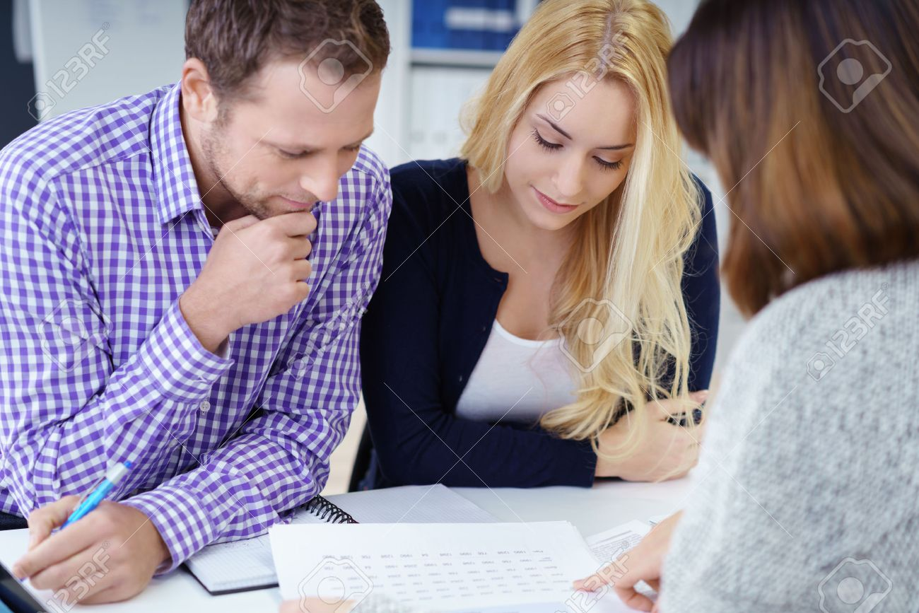 Broker giving a presentation to a young couple in her office leaning over the desk to explain paperwork to them - 51501459