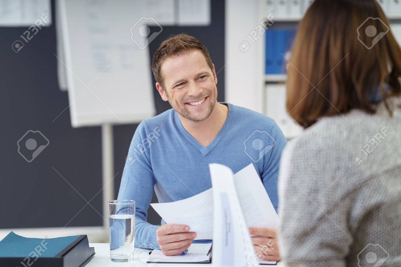 Attractive informal young businessman with a friendly smile discussing paperwork with a female colleague in the office - 51501757